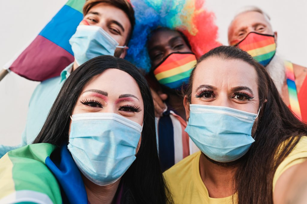 Multiracial gay friends taking a selfie at LGBT parade during coronavirus outbreak